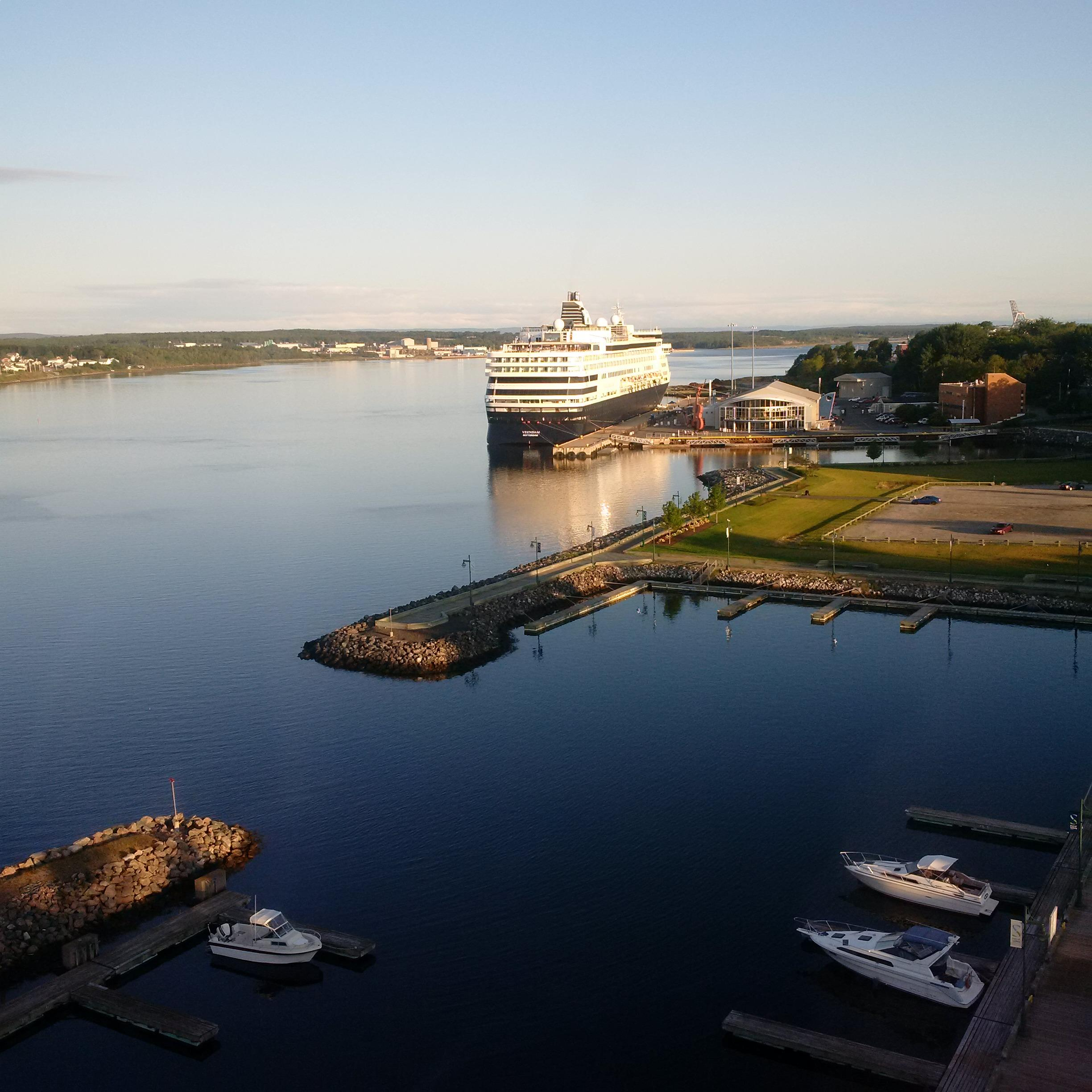 A large ship and smaller boats docked at port representing economic opportunities for Cape Breton