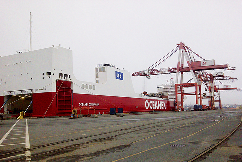 An empty cargo ship at a port with a crane in the background.